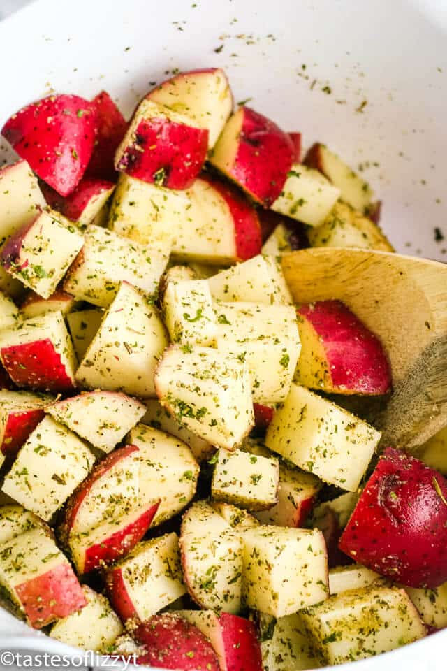 tossing diced red potatoes together with herbs and spices