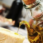 pouring some olive oil over a bread slice for an oil tasting