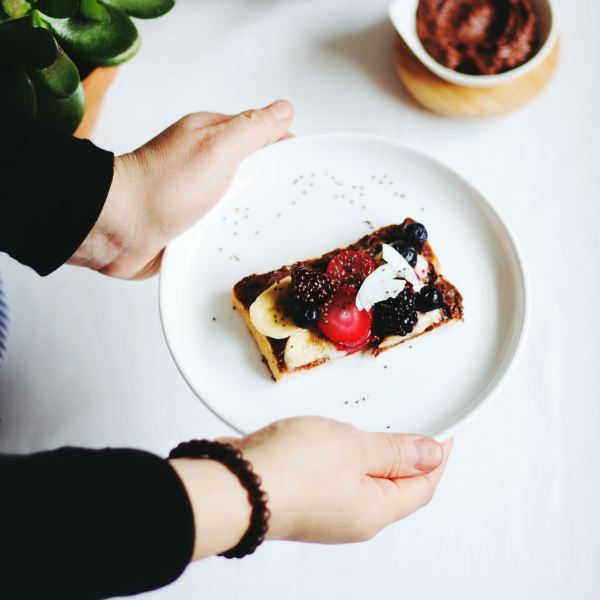 Hand holding plate of food