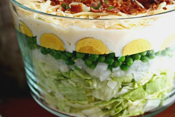 Side view of easy 7 layer salad recipe in a glass bowl with lettuce, onions, eggs. peas, cheese, and bacon