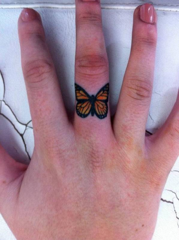 Tattoo on the finger of the girl - butterfly