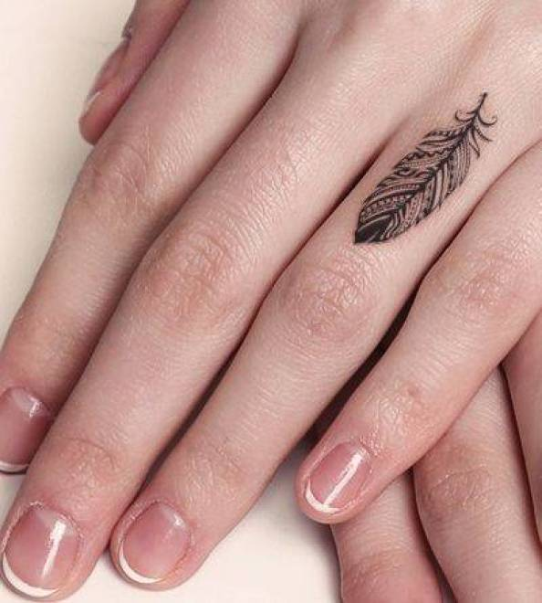 Tattoo on the finger of the girl - feather
