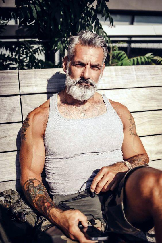 A man of a certain age with quite fresh looking half sleeve tattooes