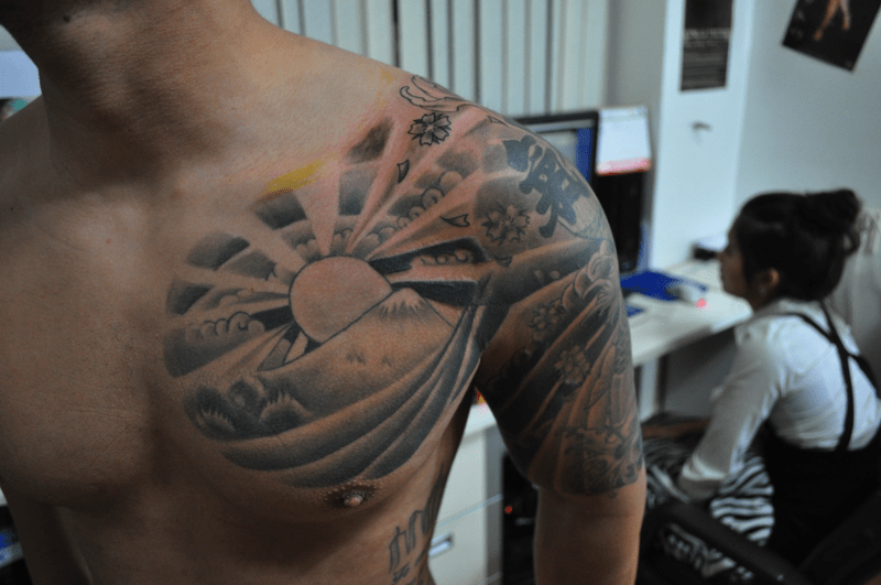 Clouds And Chest Rising Sun Tattoo