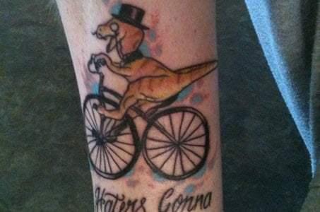 Tatuaje dinosaurio en bicicleta