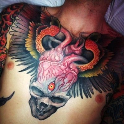 Winged skull tattoo on chest