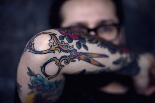 Tijera tatuada en el codo