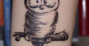 caricatura de búho tatuada en brazo