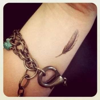 pequeña pluma tatuada en muñeca