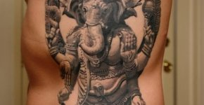 Ganesh tattoo on ribs and stomach