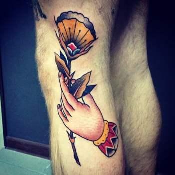 Tatuaje de una mano sujetando una flor