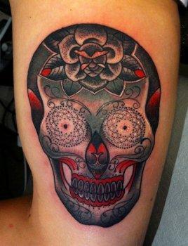 Tatuaje rostro humanoide en el muslo