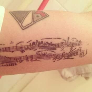Tatuaje notas musicales en el antebrazo