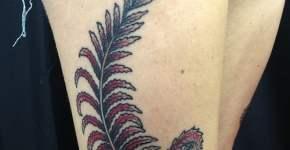 Helecho color rojo tatuado en el muslo