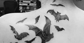 Murciélagos tatuados en la espalda alta de una chica
