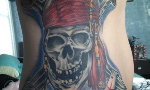 Calavera pirata tatuada en el abdomen