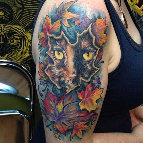Tatuaje de gato y hojas
