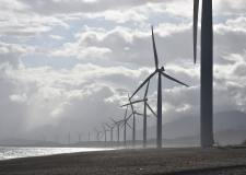 A line of wind turbines along a cost