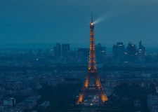 Eiffel Tower spotlight against a stormy evening sky