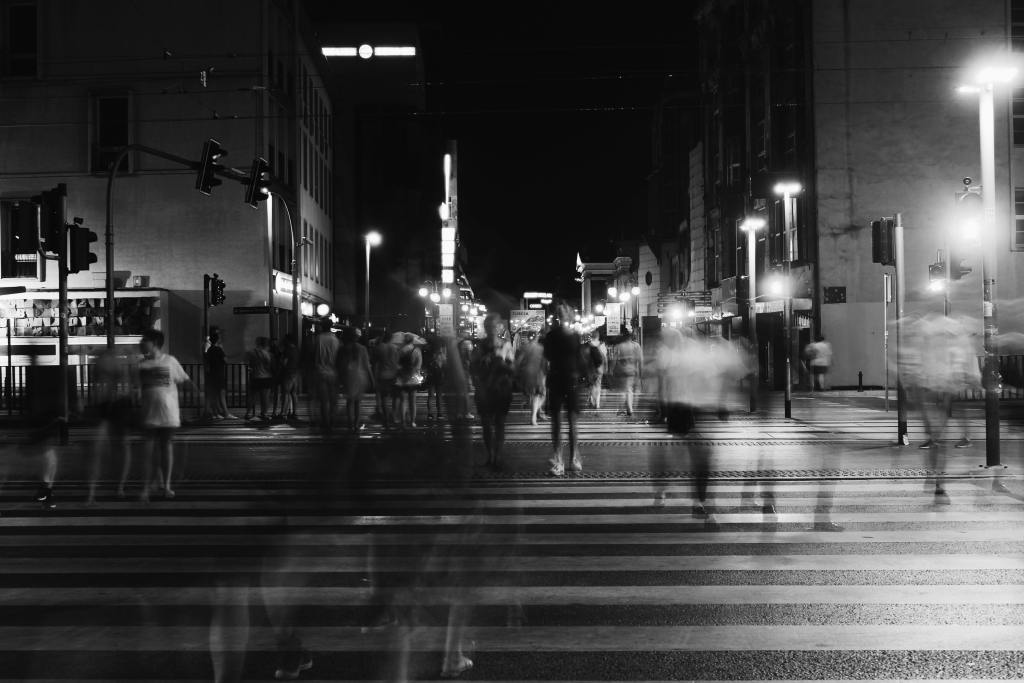 Black and white photo of a blurred people crossing a road