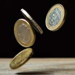 Euro coins bouncing off a table