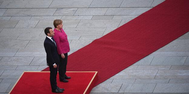 Macron steht im schwarzen Anzug neben Merkel auf einem roten Podest