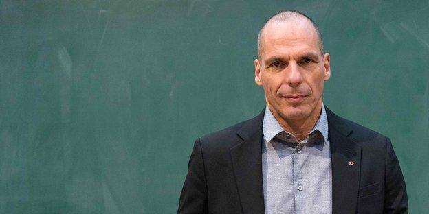 Varoufakis steht vor einer grünen Wand