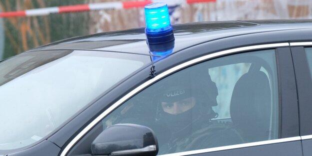 Un policía en coche de policía con luz azul.