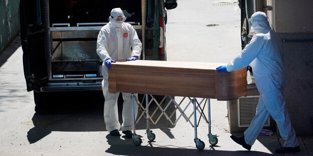 Transporting a coffin of people in protective gear.