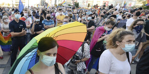 Protesters for LGBT rights in Warsaw.  They are wearing masks and a woman has stretched a rainbow umbrella over her.
