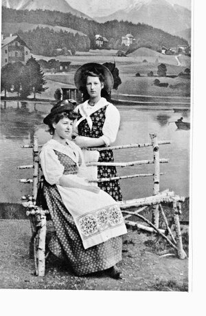 Alice as a young woman in traditional costume with her sister in a photo studio with an alpine backdrop