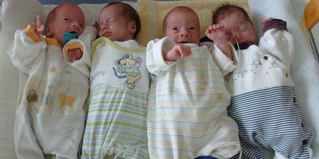 Vier Babies liegen auf einem Tuch