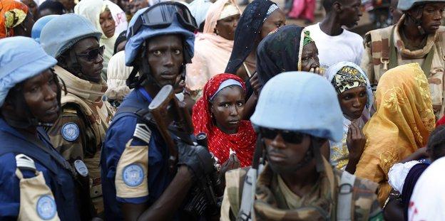 Mehrere UN-Blauhelmsoldaten in einer Menschenmenge