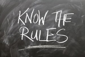 "chalkboard writing of ""know the rules"" to illustrate business compliance regulations"