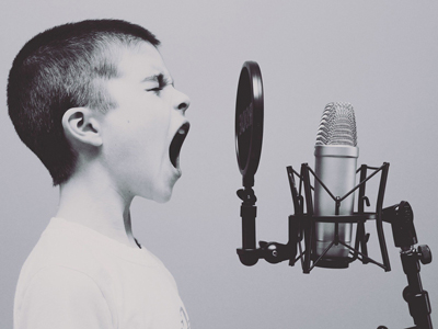 black & white image of boy with cropped hair yelling into microphone