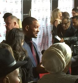 After dashing across the street to greet fans behind barricades, actor Will Smith strolls onto the red carpet with his typical grace. Smith plays Dr. Bennet Omalu, who discovered CTE among NFL players.