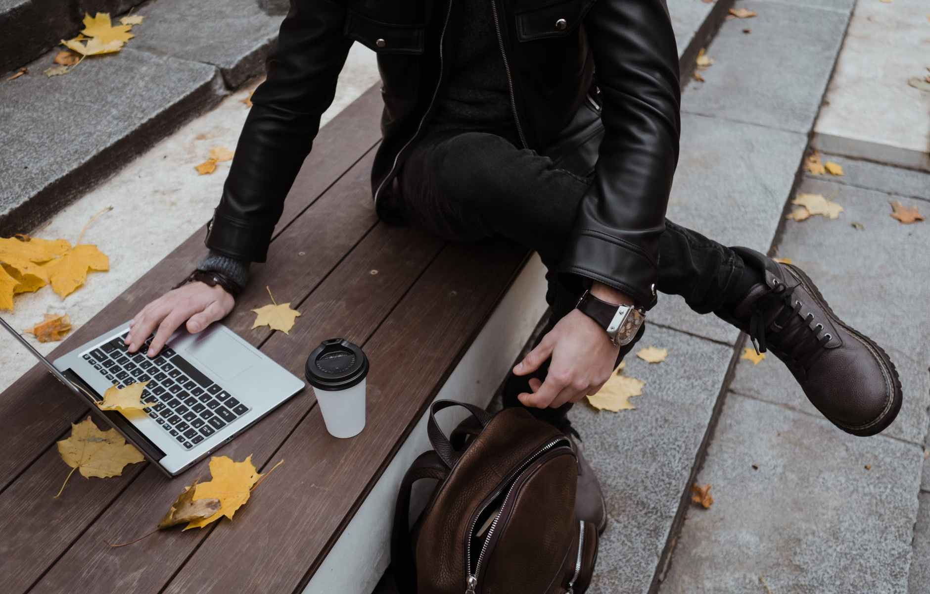 person in black leather jacket using a laptop