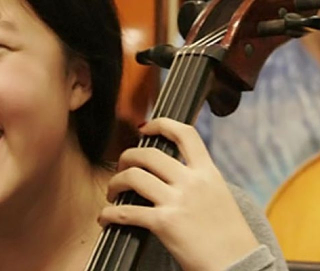 Young Girl Playing Cello In Orchestra
