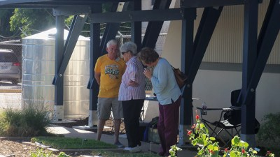 Joe Posern talks to visitors in the shade of the pergola at Demo Garden