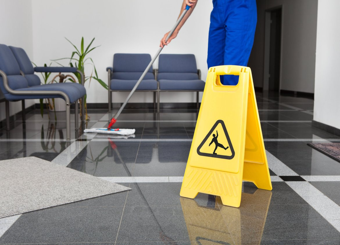 Close-up Of Man Cleaning The Floor With Yellow Wet Floor Sign