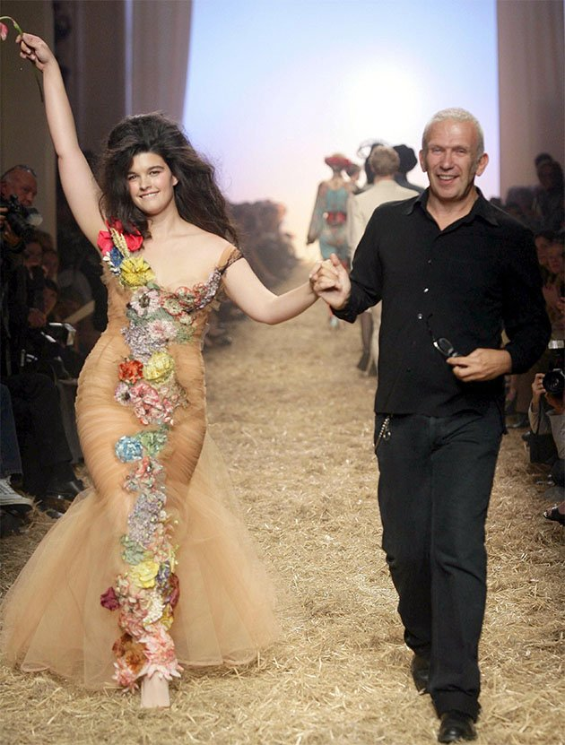 French fashion designer Jean-Paul Gaultier takes the catwalk with plus-size model Crystal Renn at the end of his spring/summer 2006 collection. (Photo by Remy de la Mauviniere/AP)
