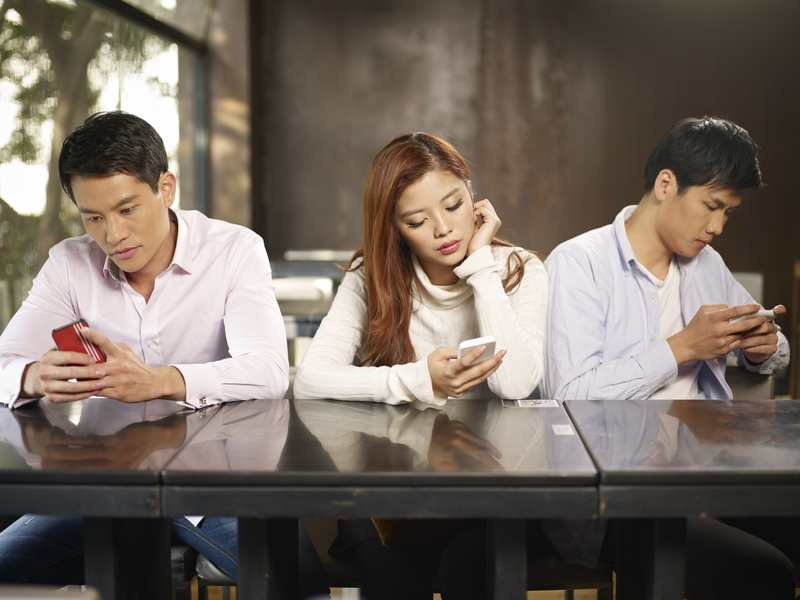 English students on smartphones waiting for teacher