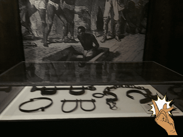 Shackles in case and Picture of Middle Passage Journey in background