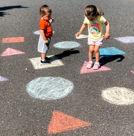 This sidewalk chalk shape & color learning game & activity incorporates gross motor & cognitive skills while your toddler or preschooler is outside playing