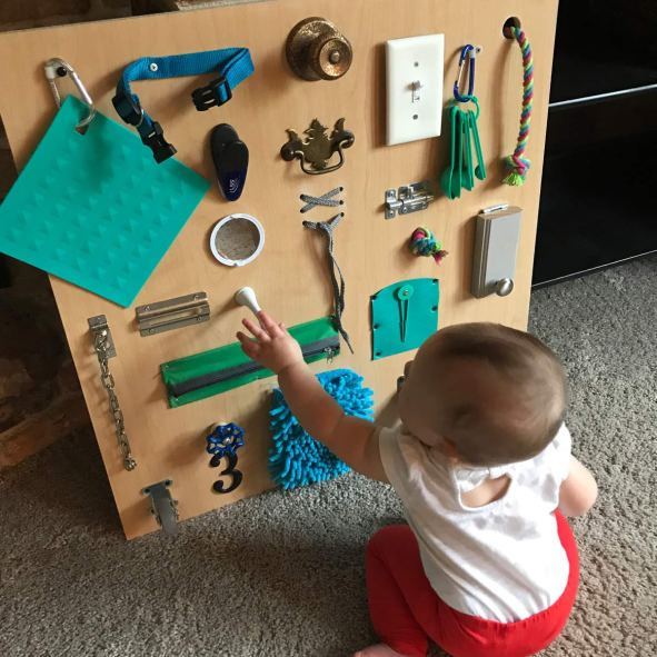 Get creative by making your own toddler busy board for your child so they can learn & explore sensory objects & toys in one place.