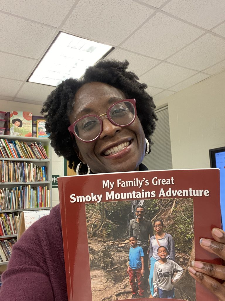 An image of me, an African American woman holding a book.  I am wearing glasses that are round with a purple-is red trim, large silver hoop earrings, a purple cardigan, and a very bright smile.  In my left hand is the book, My Family's Great Smoky Mountains Adventure.