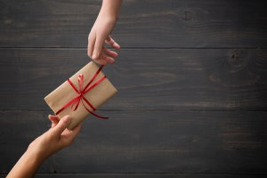 hands passing a gift wrapped in brown paper with a red bow.