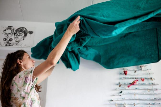 Woman shakes out blue bed sheet housecleaning tips