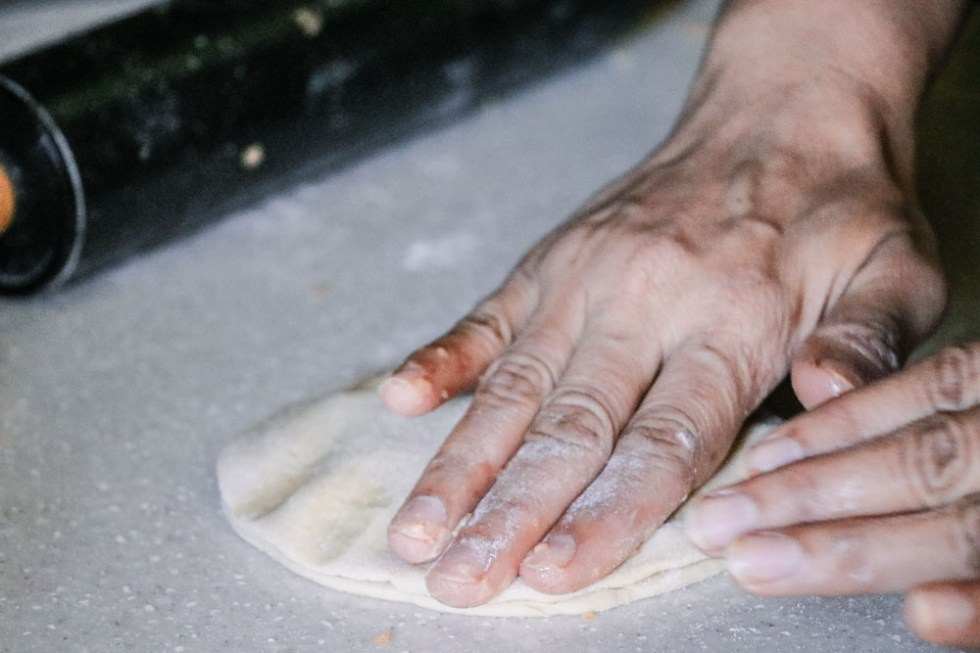 The edges of paratha dough being sealed with hands