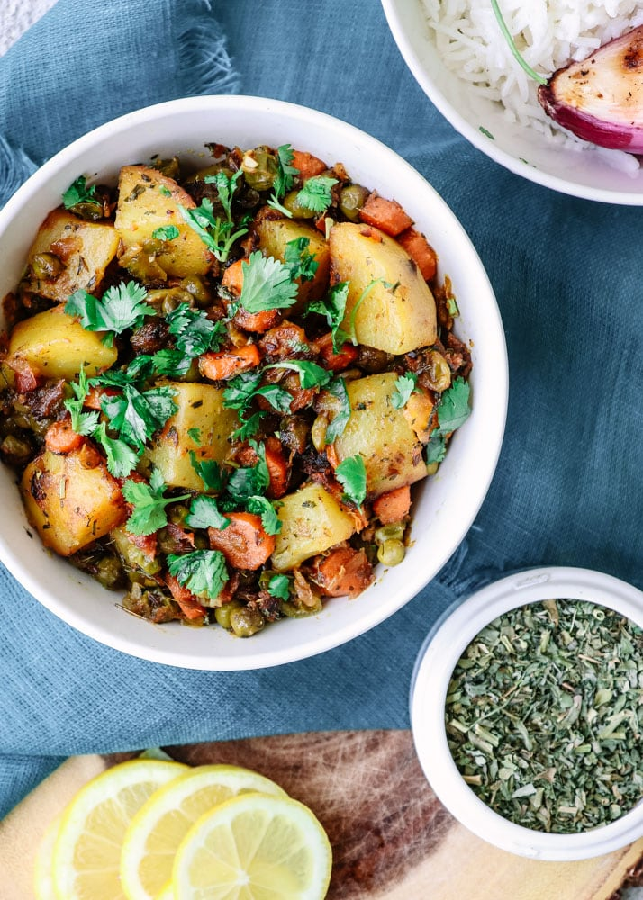 Vegan Mixed Vegetable Curry in a bowl with dried fenugreek leaves.